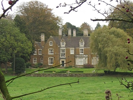 East Norton Hall through a thin autumn hedge